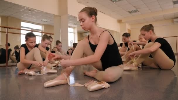 Young ballerinas put on pointe shoes in studio sitting on the floor.Dance school