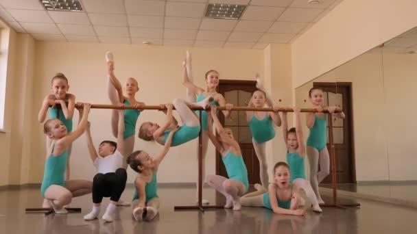 Skupina malých baletek odpočívá v baletním studiu u baletního baru.