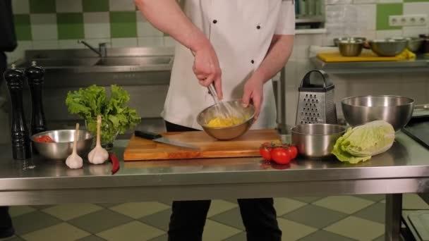 Detailní záběr profesionálního kuchaře míchání vajec v misce v kuchyni restaurace.