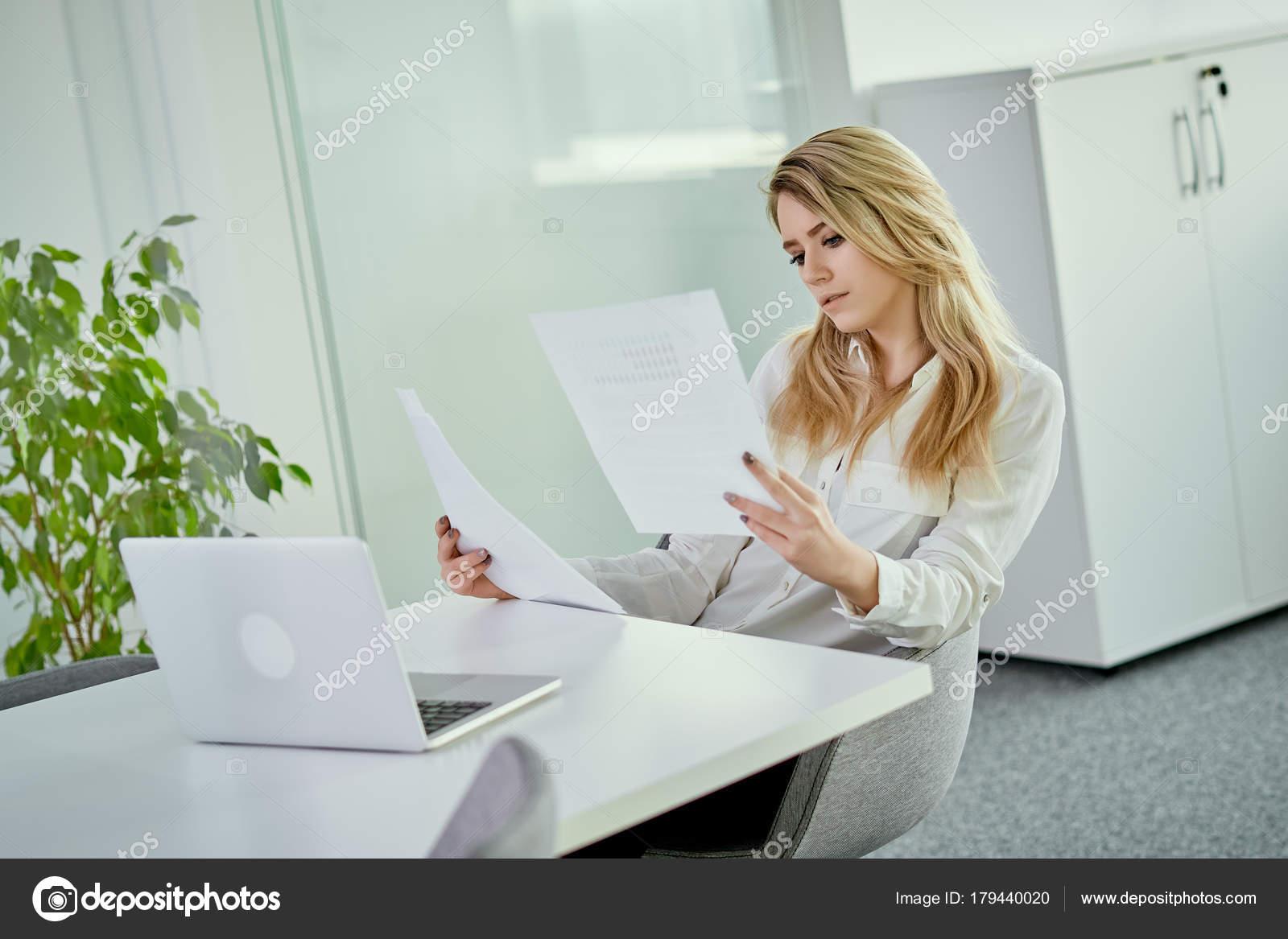 Belle jeune femme se penche sur les documents au bureau