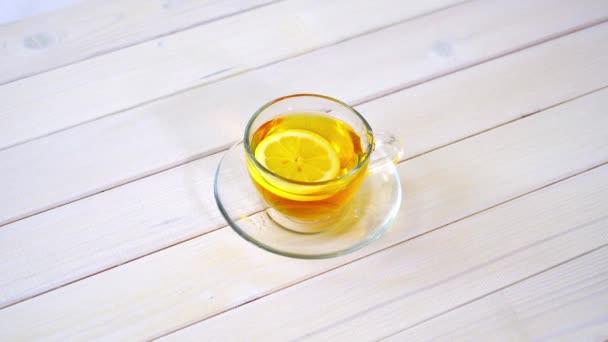 Pohár csésze hagyományos kínai tea és citromos fehér asztalon.