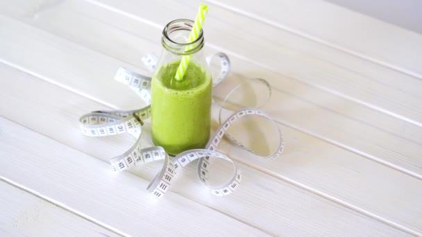 egészséges zöld és vegán koktél a fehér fa asztalon, centiméteres szalaggal