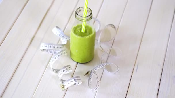 healthy green and vegan cocktail with centimeter tape on white wooden table