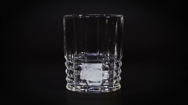 dvě kostky ledu spadnou do prázdné sklenice