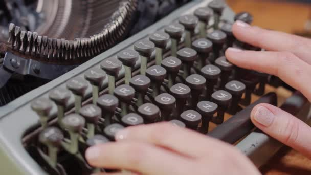 womans hands on an old typewriter