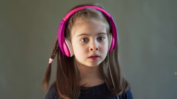 adorable girl listens to music and sings