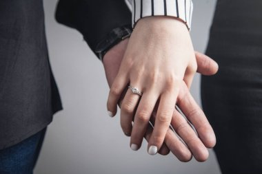 Hands of a guy and a girl with wedding ring.