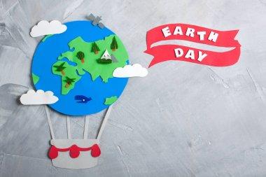 Paper craft earth globe handmade on gray concrete background.