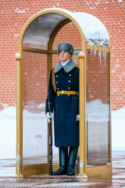 Guard of the Presidential regiment of Russia near Tomb of Unknown soldier and Eternal flame in Alexander garden near Kremlin wall. Winter view.