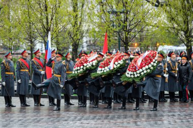 MOSCOW, RUSSIA - MAY 08, 2017: The Honor Guard of the 154 Preobrazhensky Regiment in the infantry uniform laying flowers to the Tomb of Unknown soldier and Eternal flame in Alexander garden near Kremlin wall. Rainy weather