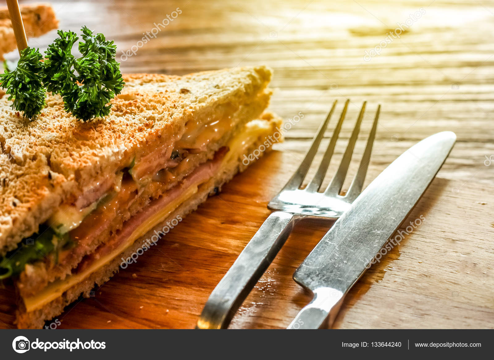Club sandwich on the wood plate decorate together with fork and knight on the bark wood table background \u2014 Photo by bookybuggy.gmail.com & Club sandwich on the wood plate decorate together with fork and ...