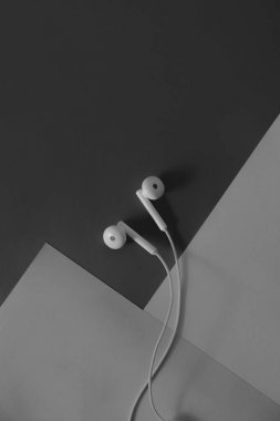 pair of in-ear headphones on dark black and white background. Top view of a wired headset against dark grey backdrop