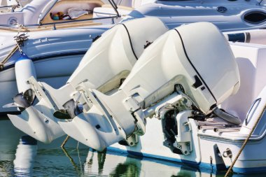 Couple of white outboard engines mounted on white boat