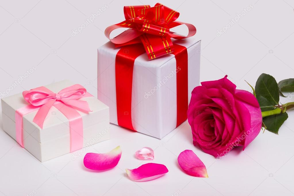 gift boxes with bows red ribbons rose and petals stock photo
