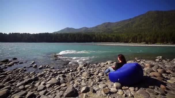 Žena se uvolňuje v židli bag na břehu řeky tyrkysové hory, Altaj, Katun