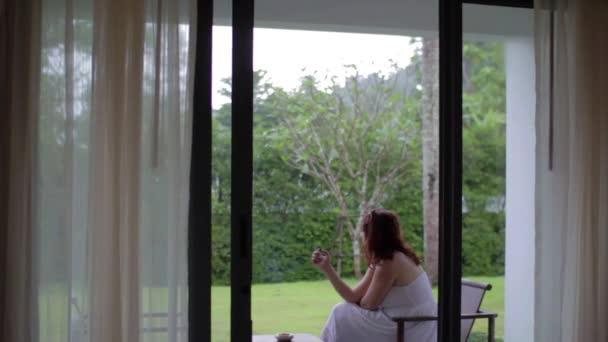 Frau mit Zigarette sitzt auf der Terrasse des Hotels