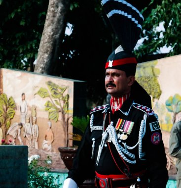 The marching Pakistani guards in national uniform at the ceremony of lowering the flags , Wagah, Lahore, Pakistan