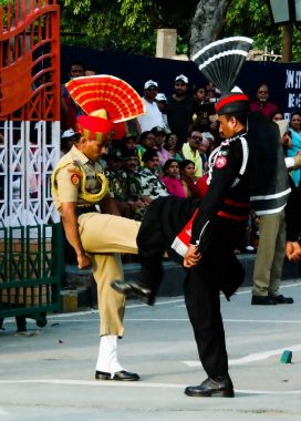 The marching Pakistani and Indian guards in national uniform at the ceremony of lowering the flags on the border between Pakistan and India, Wagah, Lahore, Pakistan