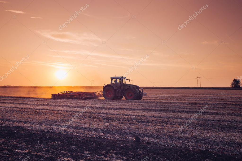 tractor plowing during sunset