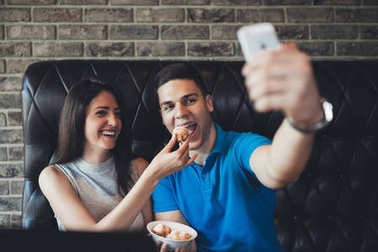 Attractive young couple having good time in cafe restaurant. Young man holding a cellphone and making selfie
