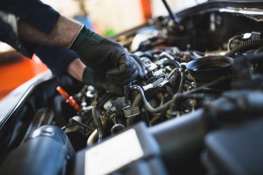 Car service mechanic working on automobile engine repair