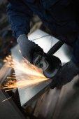 Metalurgie těžký průmysl. Továrna na výrobu těžkých pelety kamna a kotle. Pracovník se zblízka. Extrémně tmavých podmínkách a viditelný šum