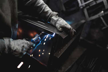 Metallurgy industry. Factory for production of heavy pellet stoves and boilers. Close up of manual worker welder on his job. Extremely dark conditions and visible noise