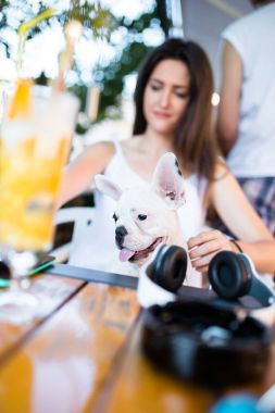 Beautiful young woman sitting in cafe with her adorable French bulldog puppy. People with dogs theme