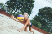 Photo Young beautiful woman playing beach volleyball on sunny day.