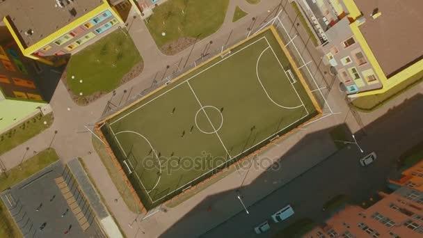 Nad horní pohled děti hrát fotbal na školní stadion letecké 4 k Uhd