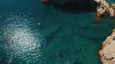 Aerial shot of sea waves and cliff. Sveti Nikola Island rock coast drone footage