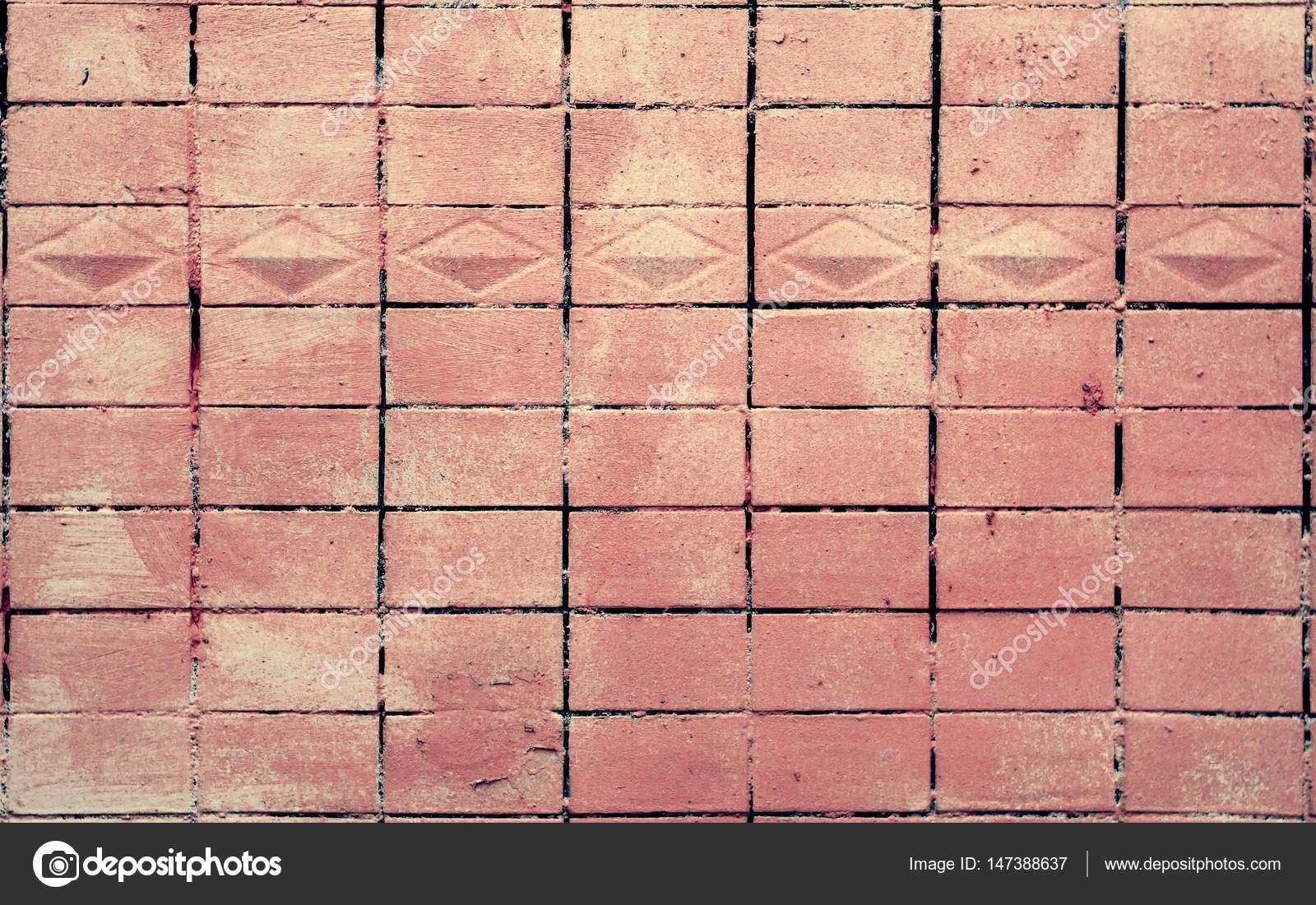 Vecchio dipinto nella struttura della parete di mattonelle rosse