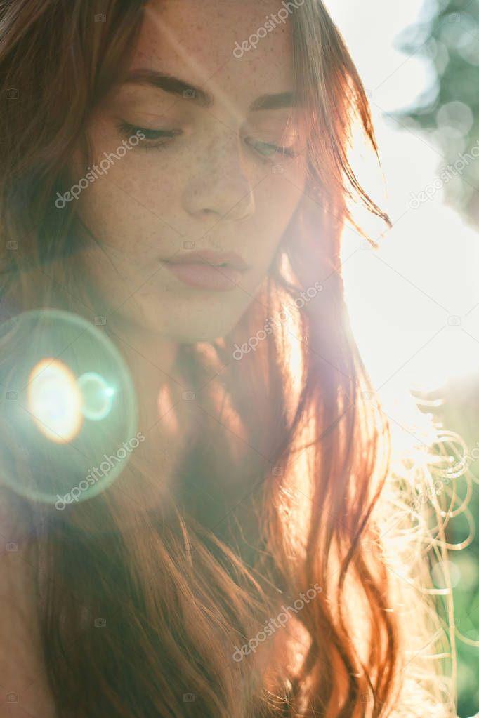 Beautiful redhead girl in sun rays