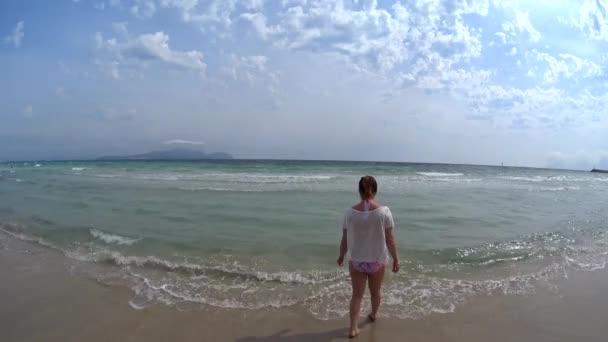 schönes Mädchen mit rosa Bikini, Sonnenbrille und weißem T-Shirt, das in den Untiefen des Strandes plantscht, Mädchen, die ihren Strandlebensstil genießen, indem sie am aquafarbenen Meer entlang gehen, Mallorca, Spanien