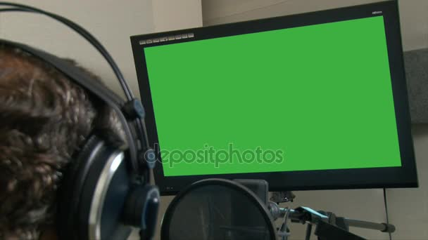 Photo Closeup shot man head in headphones reading text from a green screen monitor