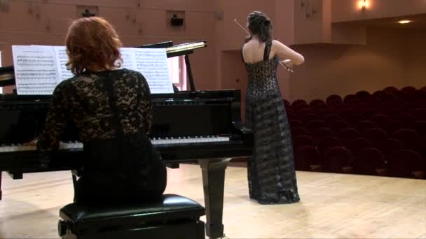Violin and piano musical duo on the scene, two girls playing on the stage