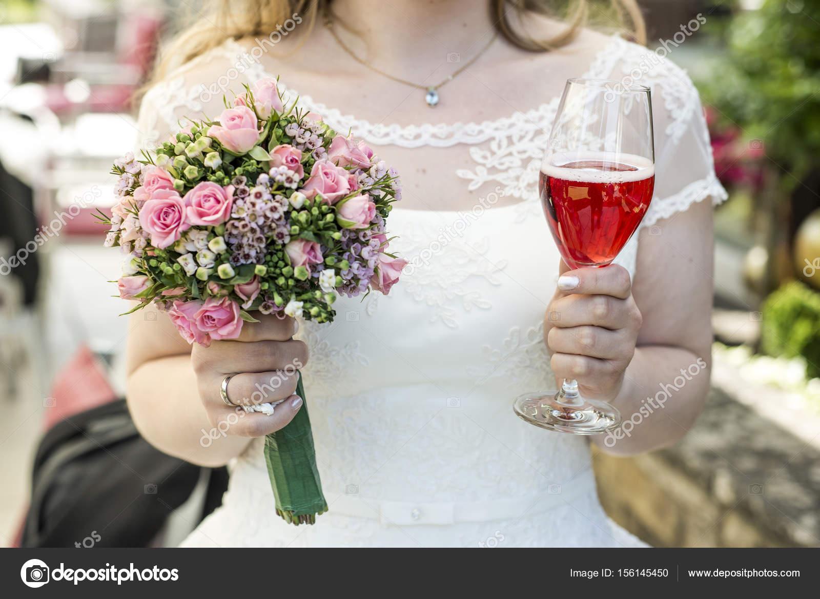 921a55f8fef9 Bruden håller bukett blommor och ett glas vin närbild bröllop äktenskap–  stockbild