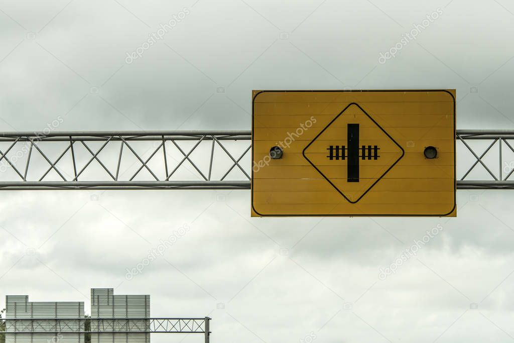 Railroad crossing warning attention lights sign front of cloudy sky in canada