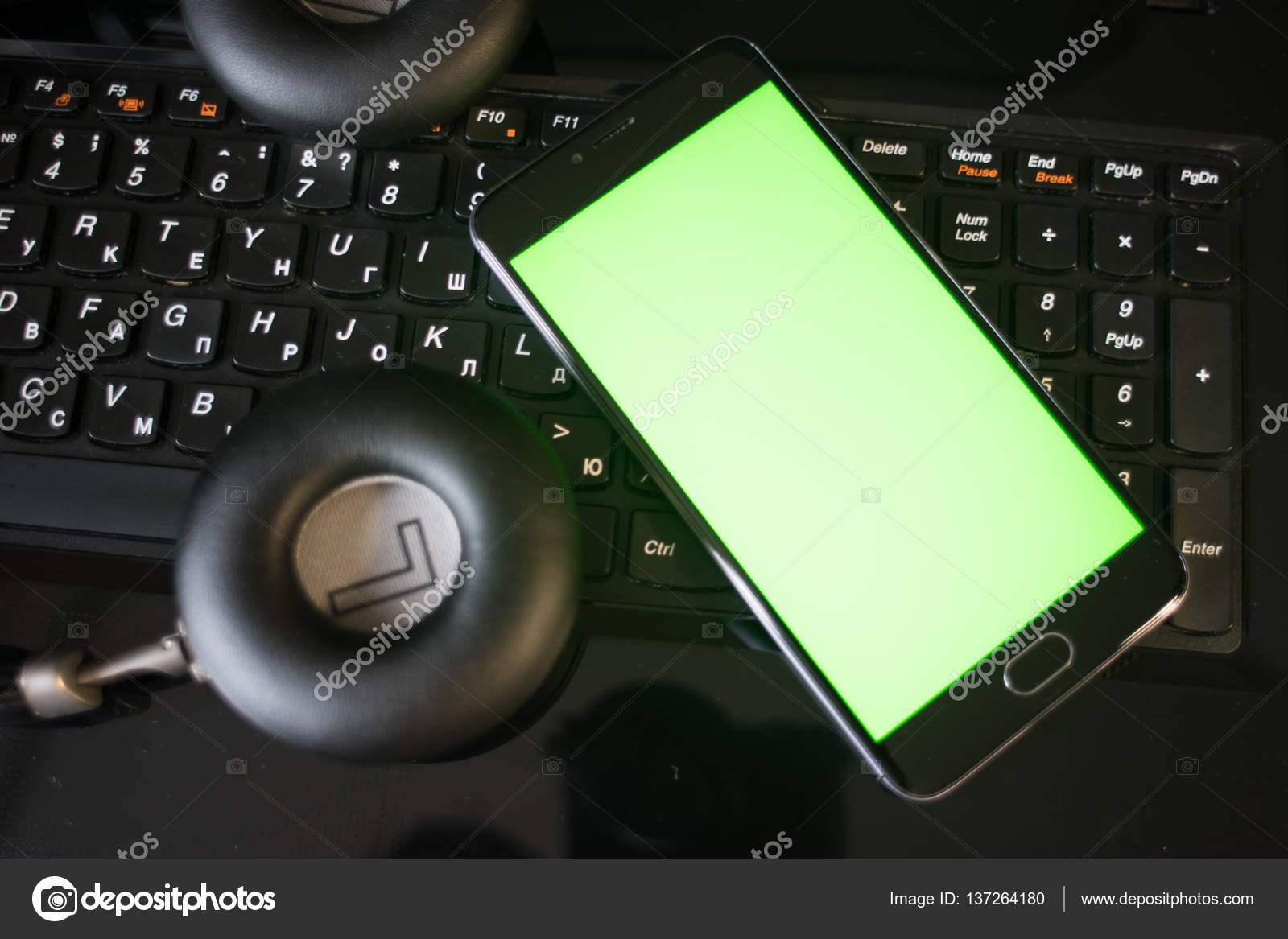 Laptop and headphones smartphone with green screen — Stock