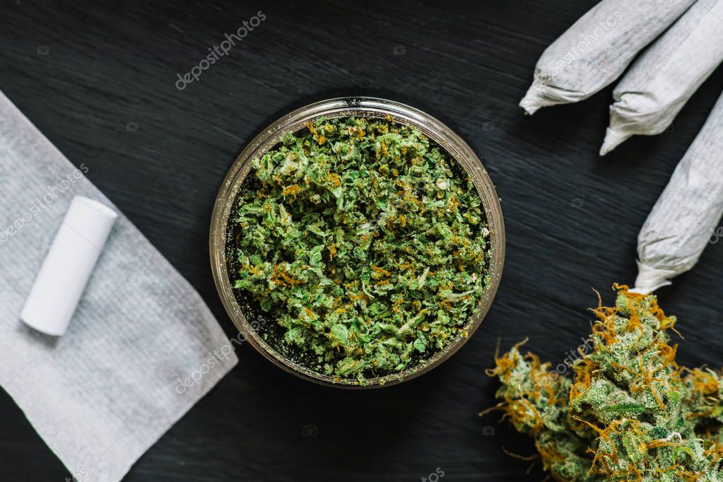 Grinder for chopping cannabis flowers with fresh weed surrounded by joint and paper for a self-rolled on a black background wooden texture