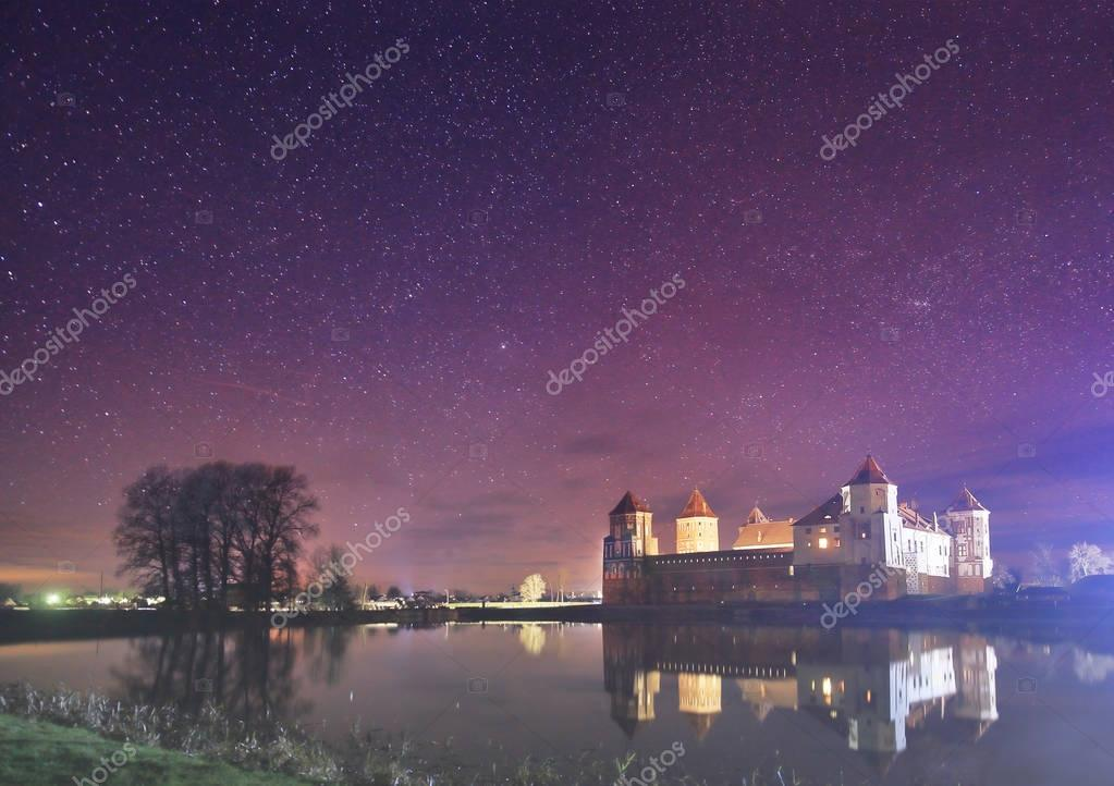 Night landscape of the old castle in the background of the starry sky and the lake.