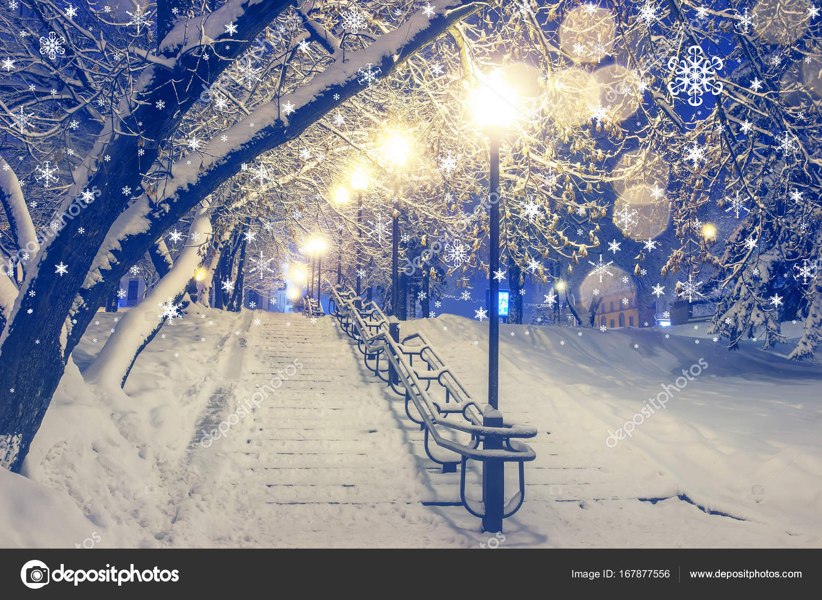 Lanterns in winter park in the evening. Beautiful snowfall for ...