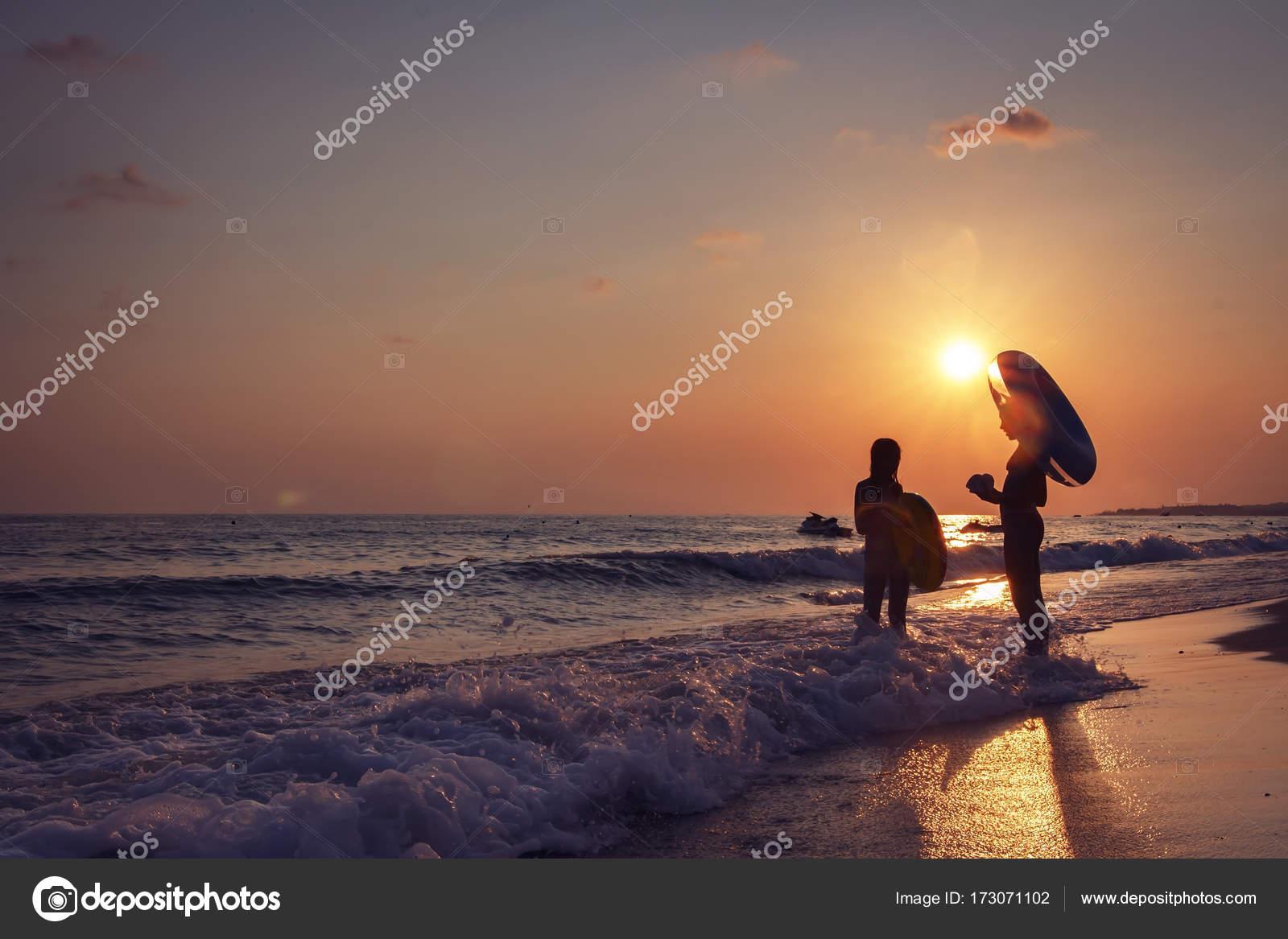 bccd5b3d4 Dos chicas jóvenes relajación en la playa al atardecer. Olas en la playa.  Bañarse en el mar al atardecer– imagen de stock