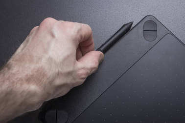 Graphic tablet with pen close-up. The artist's hand with graphic tablet.