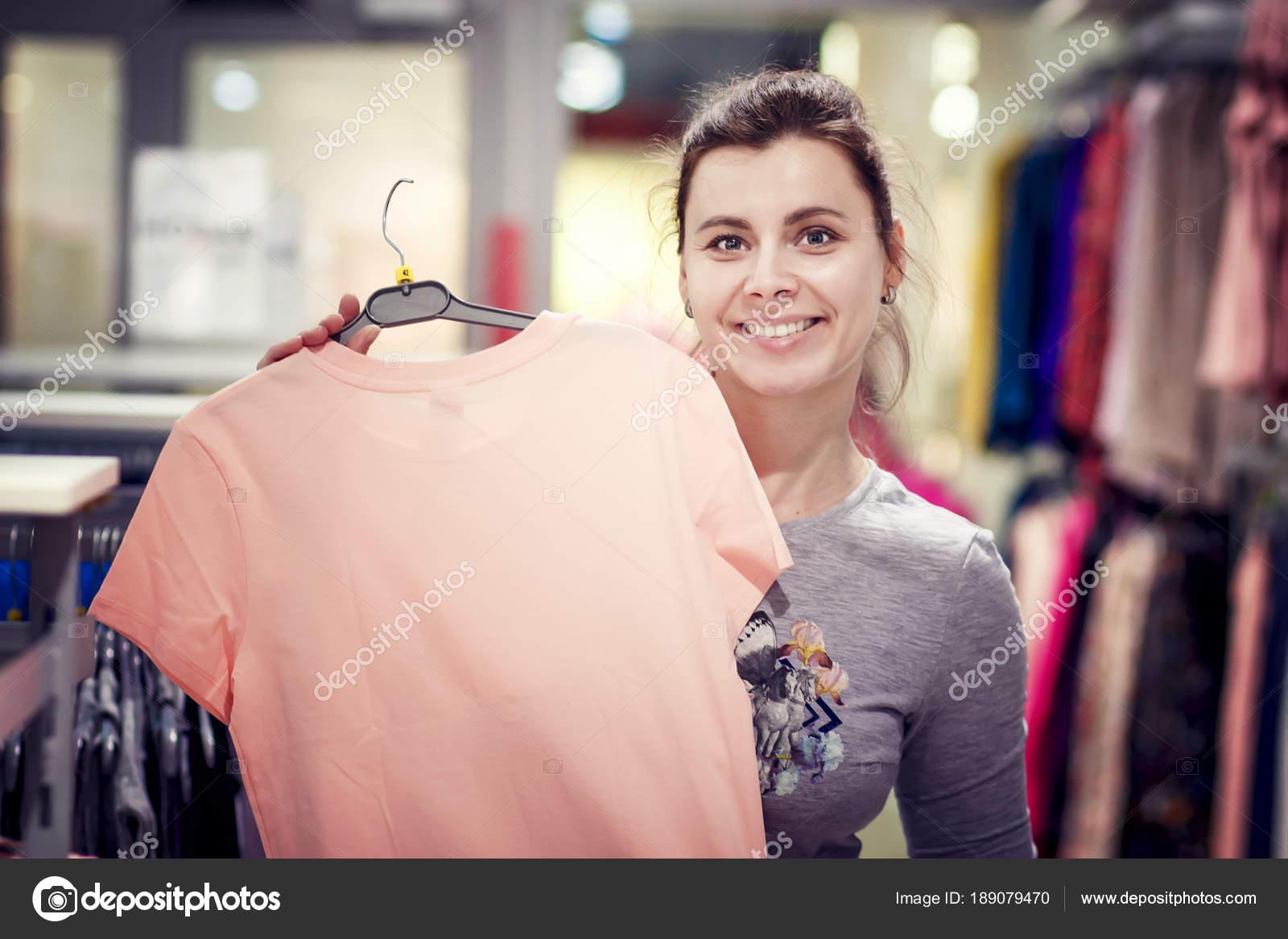 Chica feliz tiene una nueva camiseta en percha en tienda de moda ...
