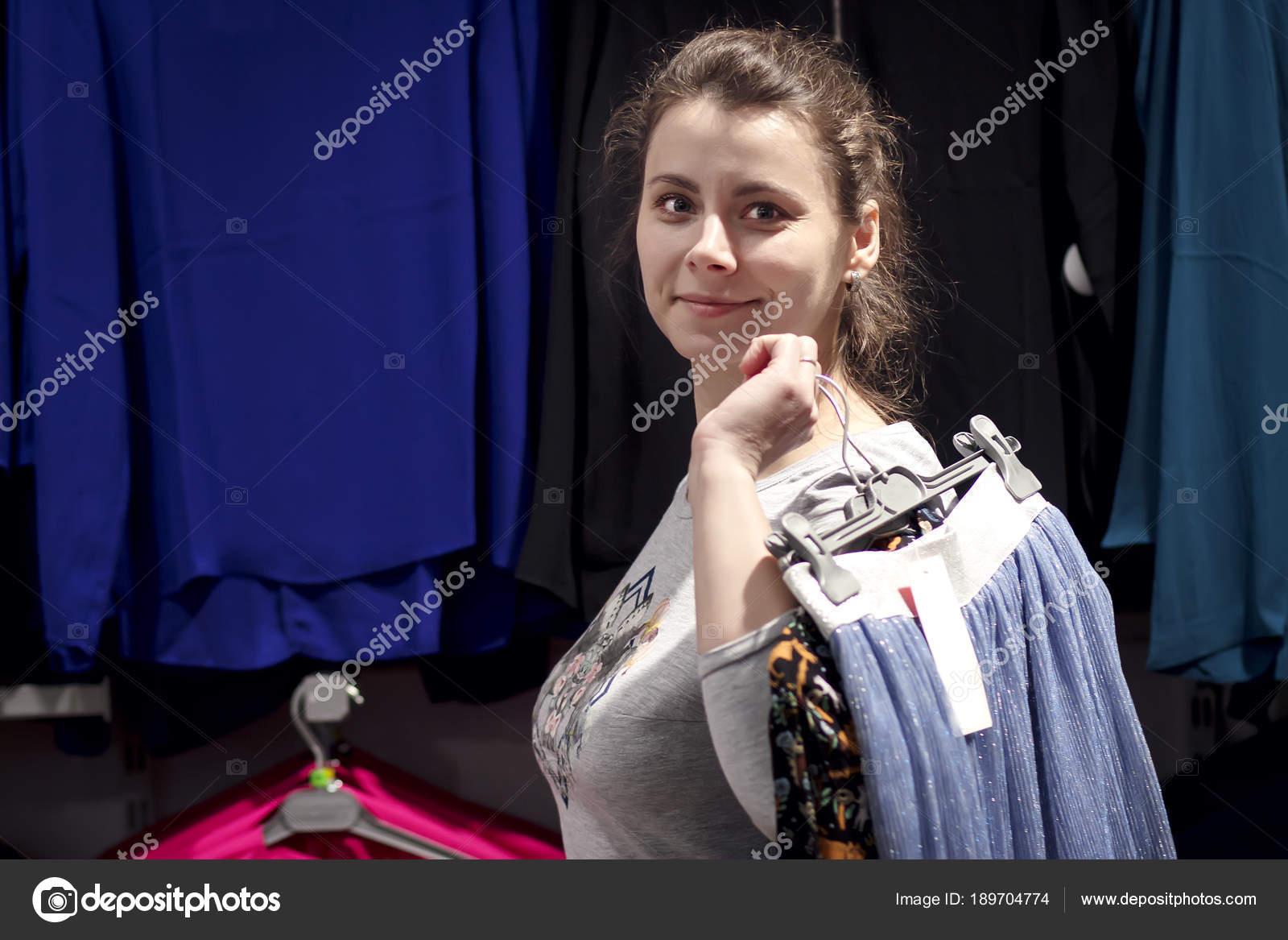 4fb95a659de02 Genç kız kıyafetleri şık butik dükkan satın alır. Alışveriş kavramı. Kız  giyim mağazası şeyler askı tutuyor. Yeni elbiseler satın alma ...