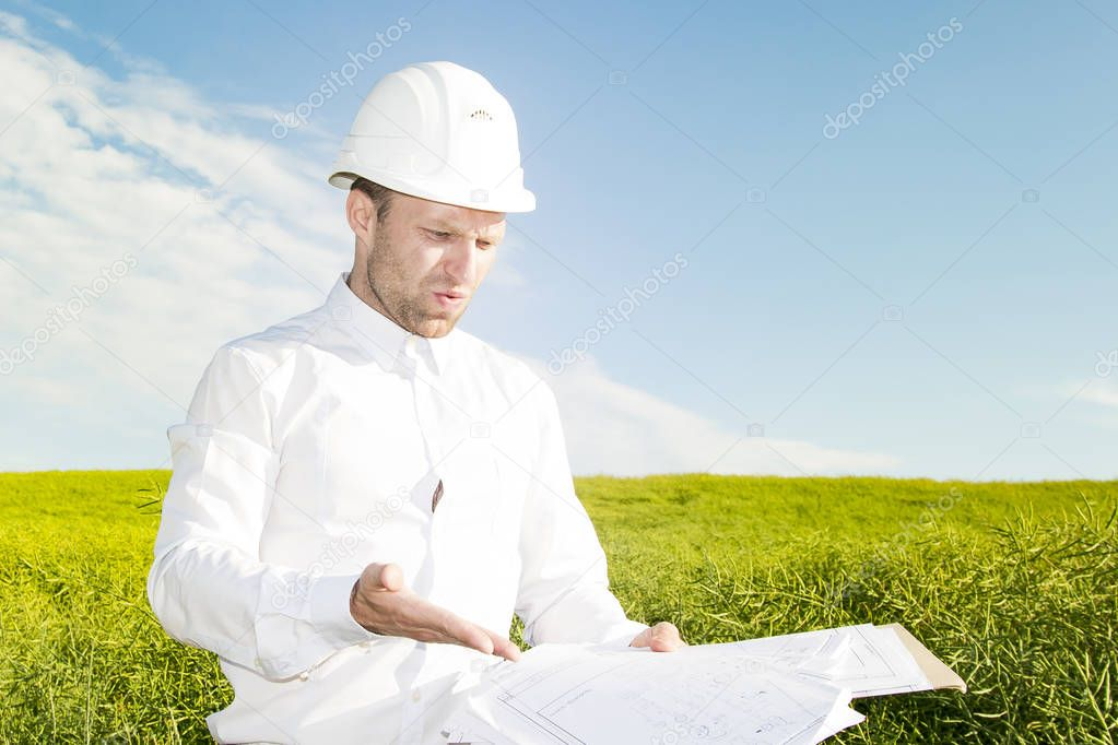 Engineer builder is dissatisfied with poor project documentation. Worker with blueprints on background of meadow and blue sky with white clouds during day. geodesist chooses site for construction.
