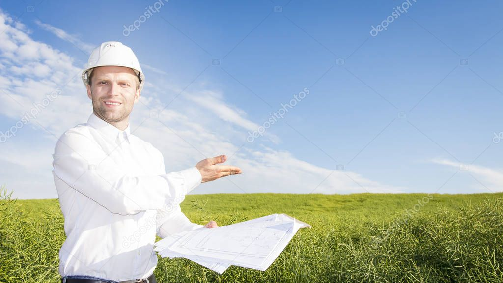 Geodesist with drawings on ground for building building. Builder in white helmet and project documentation on green meadow. soil scientist examines earth and soil Engineer points to construction site.