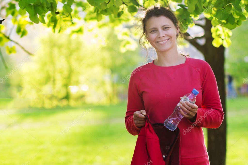 Happy attractive brunette girl with water bottle and backpack in green city park before training fitness. Healthy lifestyle concept. playing sports in nature. Woman smiling in front of yoga.