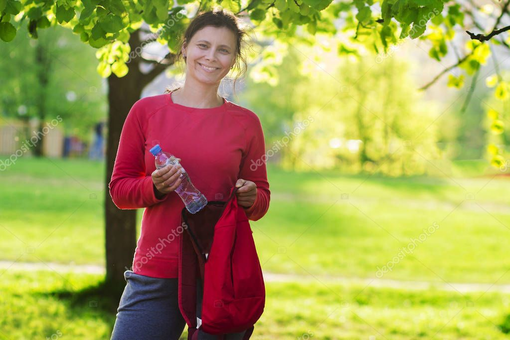 Beautiful smilling girl in sportswear in green park on sunny day with bottle of water and backpack. Young brunette woman in city park after yoga classes.